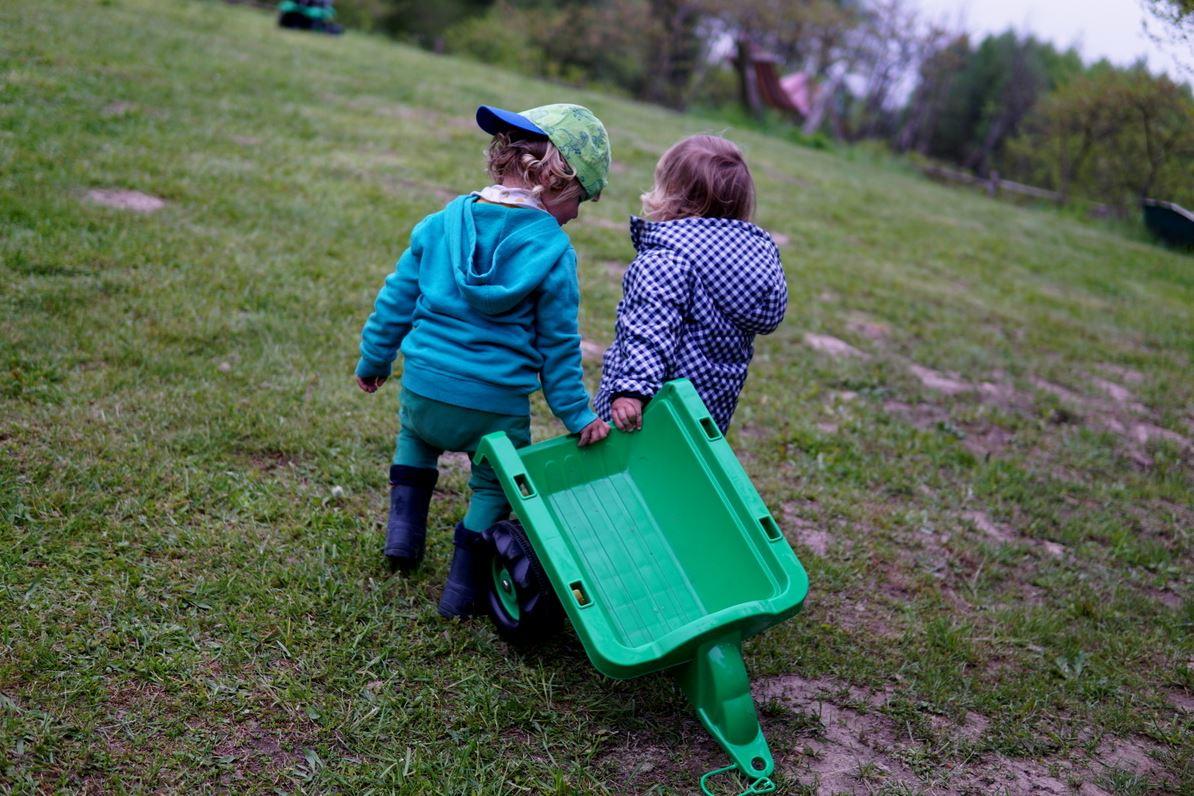 Deux enfants jouant avec la remorque en plastique d'un tracteur