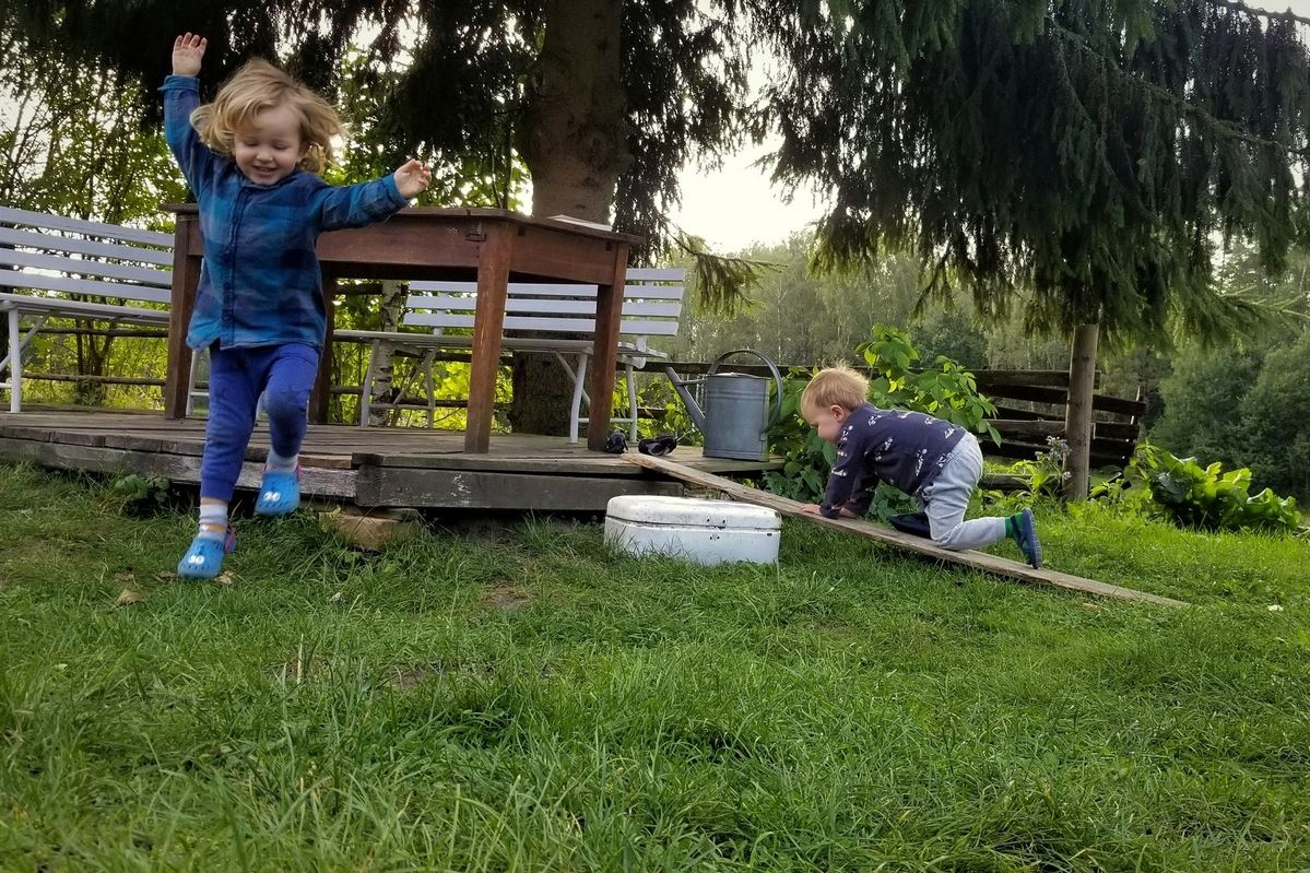 Kids playing with wooden board in summer